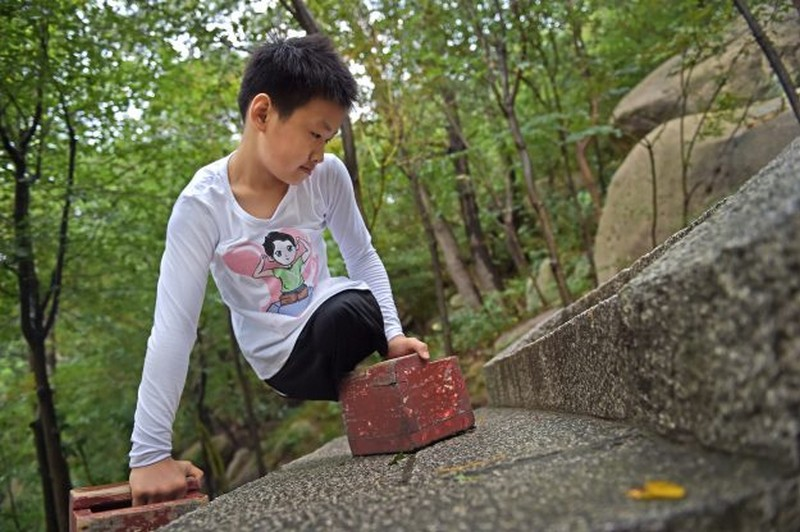 Wanderlust Tips Magazine | 11-year-old legless boy conquered 900m high moutain in China